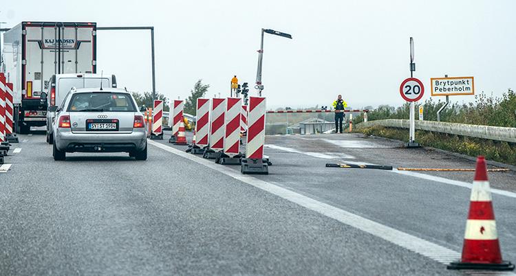 en gränskontroll vid pepparholmen i damark. Bilar på kö på en väg. Bakom en avspärrning syns en person med arbetskläder.