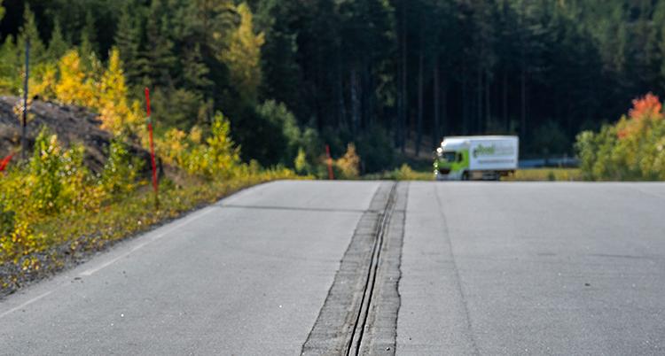 En skena löper i asfalten. I horisonten syns en lastbil. Vid sidan av vägen är skogen höstfärgad.
