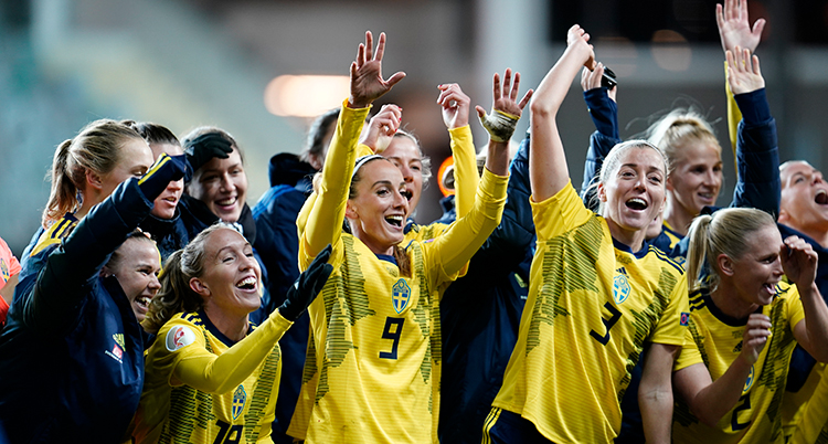 Flera svenska spelare jublar och håller upp händerna. De står tätt tillsammans.