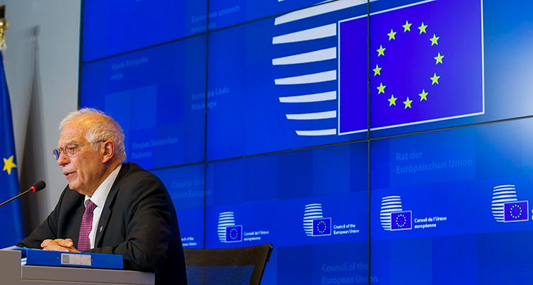 EUs utrikeschef Josep Borrell sitter vid podiet framför en blå skärm med EUs flagga.