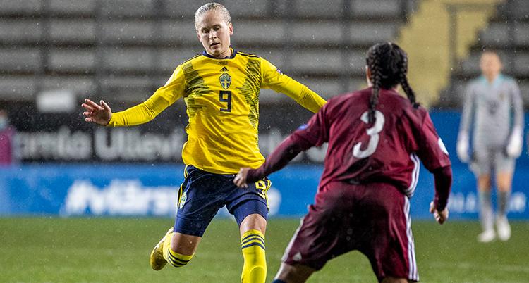 en fotbollsspelare i gul tröja möter en fotbollspelare i vinröd tröja