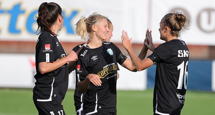 Tre spelare i Göteborg firar ett mål. De trycker händerna mot varandra. De har svarta dräkter.