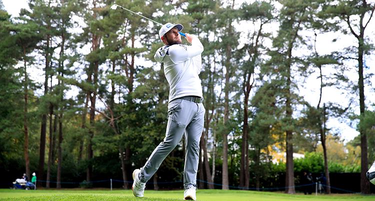 En man som har en ljus tröja med huva på sig svingar en golfklubba.