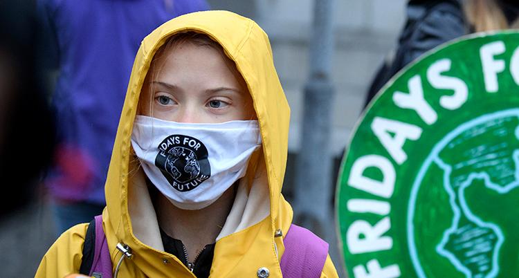 Greta står med gul regnjacka. Hon har munskydd. På det står Fridays for future.