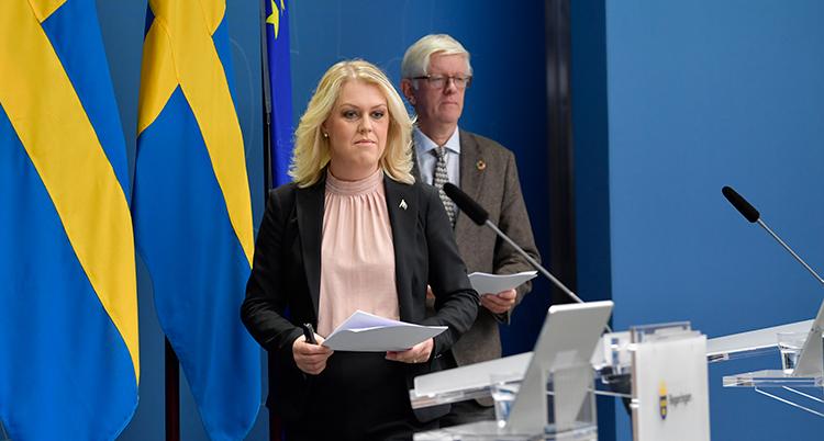 En kvinna går mot en mikrofon. Bakom hennes syns en man och svenska flaggor.
