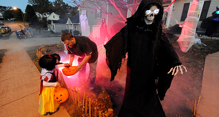 Ett litet barn tar godis från en skål. Ett skelett i svarta kläder syns också på bilden.