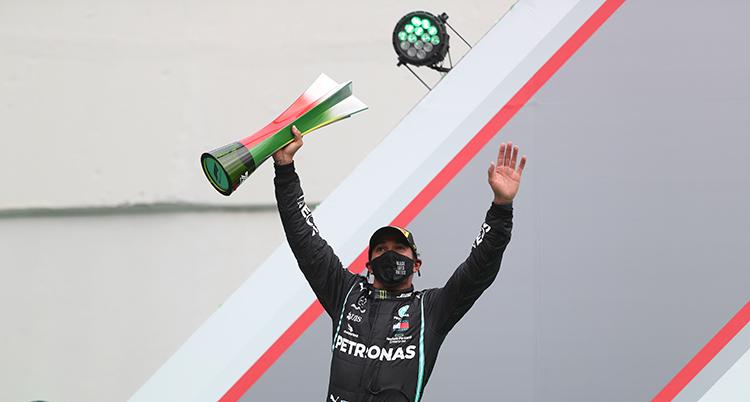 Lewis Hamilton sträcker armarna mot luften. I ena handen har han en pokal.