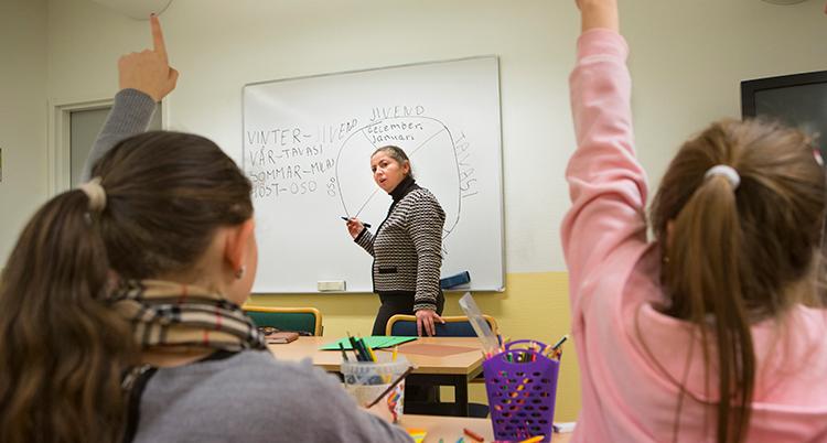 en lärare skriver på vita tavlan i ett klassrum. Två barn med ryggarna mot kameran räcker upp handen.