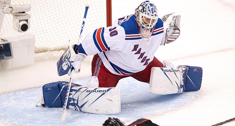 Lundqvist räddar ett skott. Han har benen brett isär och armarna ute.