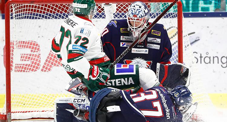 Hockeyspelare i hockeyutrustning ligger på varandra framför målvakten i ett hockeymål