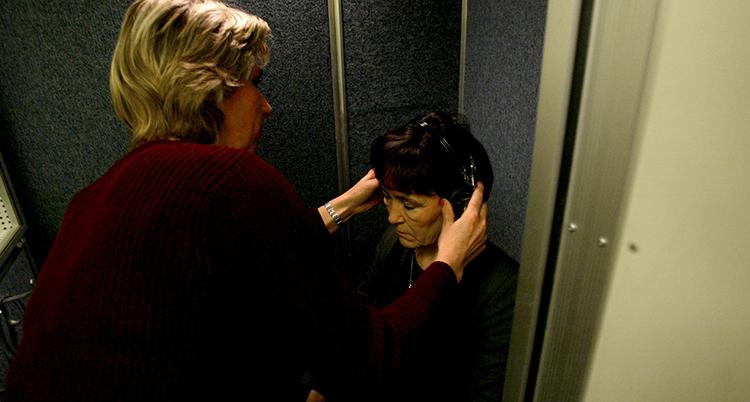 En kvinna sätter på en annan kvinna ett par hörselkåpor, hon ska testa sin hörsel