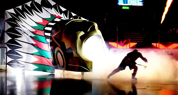 En ishockeyspelare åker ut på isen genom en port som har utseendet av en indianplym.