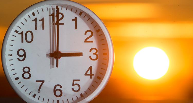 En stor klocka som visar kl 3. Bakom syns en soluppgång.