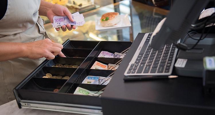 En kassa med sedlar. Någons händer tar upp pengar från kassan.