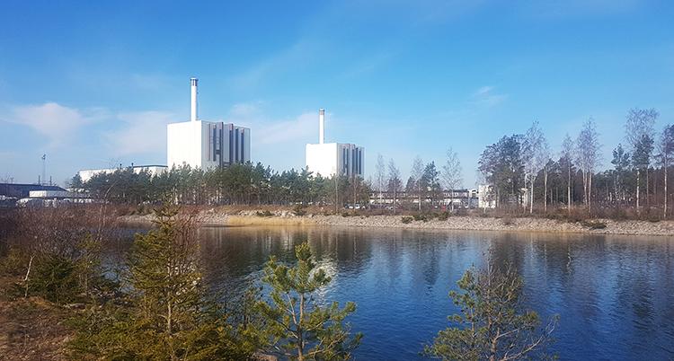 Två vita kraftverk. Fyrkantiga med höga skorstenar. Framför dem är en sjö.