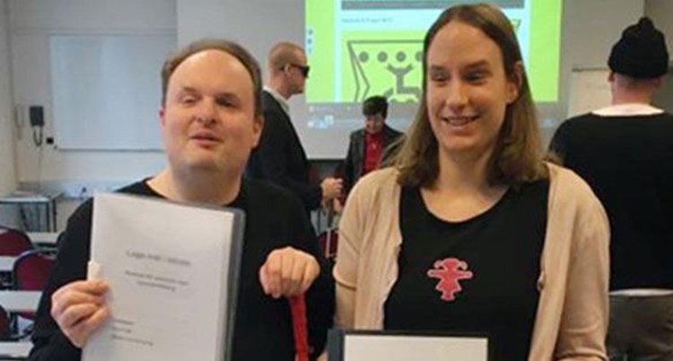 En man och en kvinna står bredvid varandra i ett klassrum.