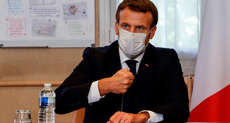 Macron sitter vid ett skrivbord. Han har kostym och munskydd på sig,