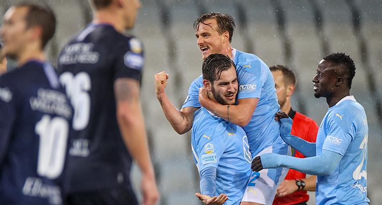 Tre spelare i Malmö kramar varandra. En har hoppat upp i famnen på ens annan. Deppiga göteborgare står bredvid.