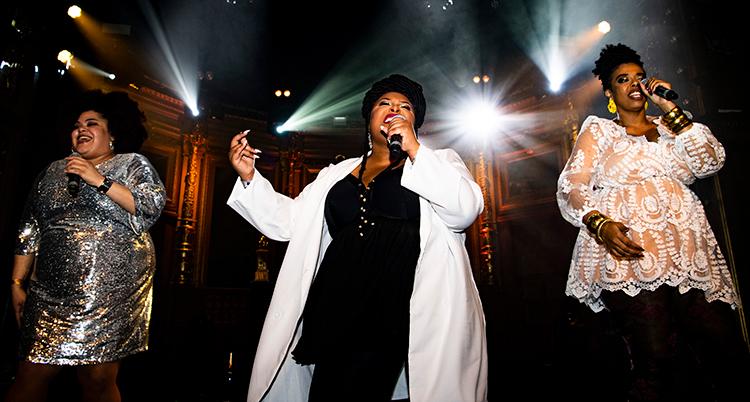 Tre sångerskor sjunger på scenen. Bakom cdemn är strålkastare. Alla har fina kläder på sig.