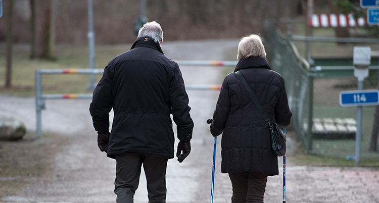 Tv å gamla personer är ute och går på en väg. En dem har stavar i händerna.