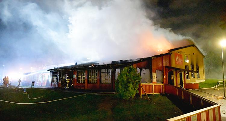 Massor av rök stiger från husets tak. Huset är rött. DEt är kväll och mörkt på bilden.
