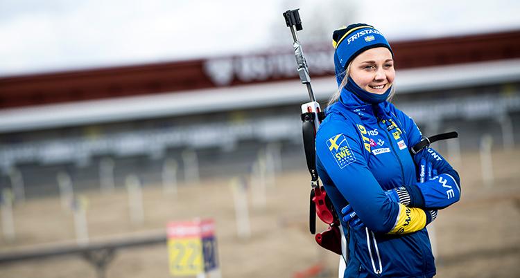 Stina Nilsson står med armarna i kors. På ryggen har hon ett gevär för skidskytte.