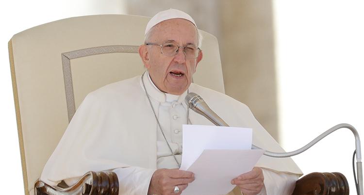 Påven i vitt läser från ett papper.