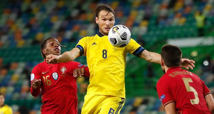 En svensk spelare hoppar och har bollen framför bröstet. Två portugiser försöker att nå bollen.