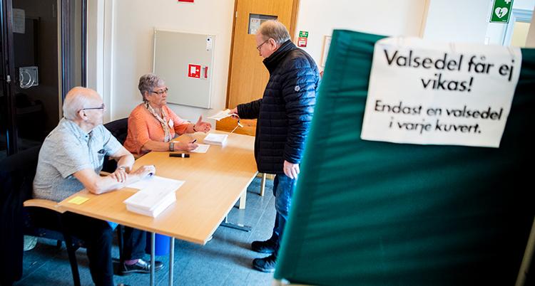 En man lämnar sin röst till röstmottagare som sitter vid ett bord. I förgrunden ett röstbås.