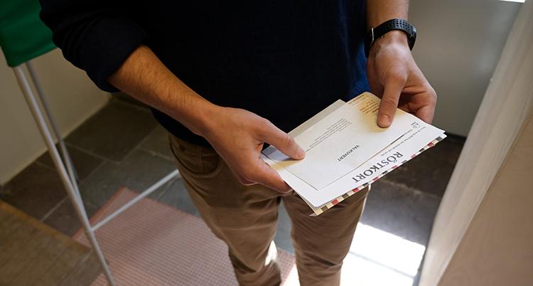 En person med röstkort i händerna.