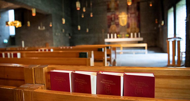 Psalmböcker som står på en hylla i en bänk i en kyrka