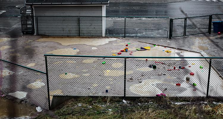 En bild på en liten skolgård med staket runt. Den är tom. Lite leksaker ligger på marken.