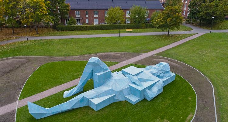En skulptur i form av en lång, ljusblå person av betong ligger utsträckt i grönt gräs