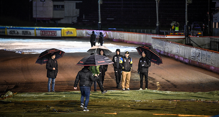 Människor står med paraplyer på en speedwaybana.