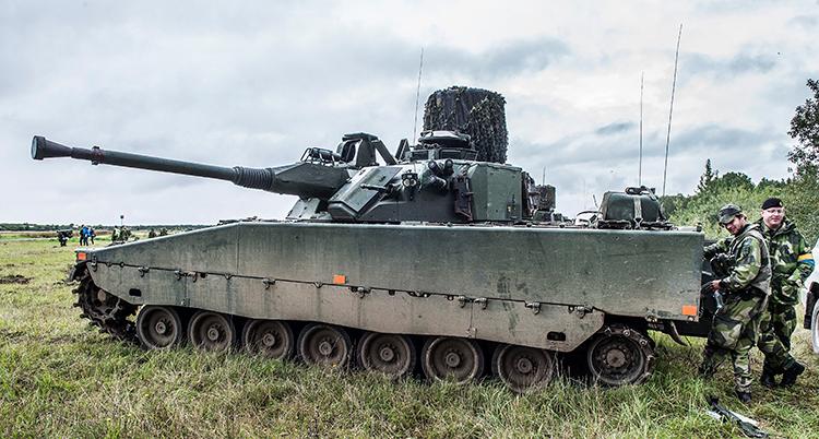 Några militärer står i gröna kläder runt ett stor stridsvagn. Den har flera hjul. De över på en stor gräsmatta.