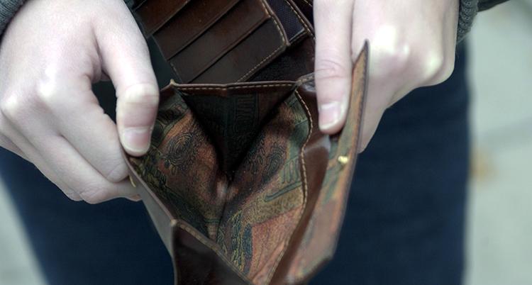 En kvinna håller upp en tom plånbok. Den är brun.