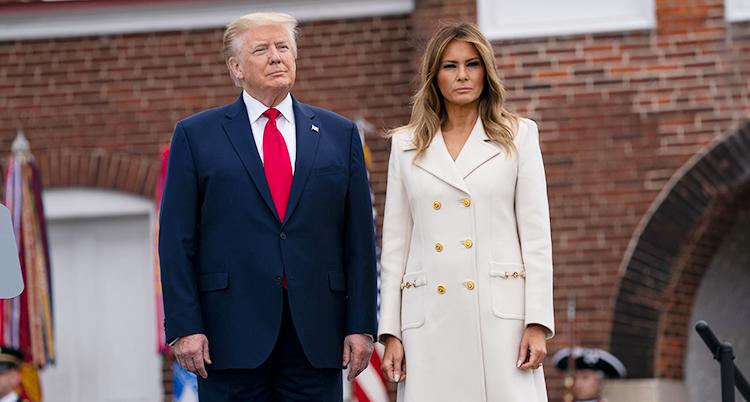 Det står bredvid varandra. Han har mörkblå kostym och röd slips. Hon har en vit kappa på sig.