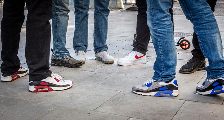 Benen på unga människor med jeans och på fötterna gympaskor. De står nära varandra i en klunga.