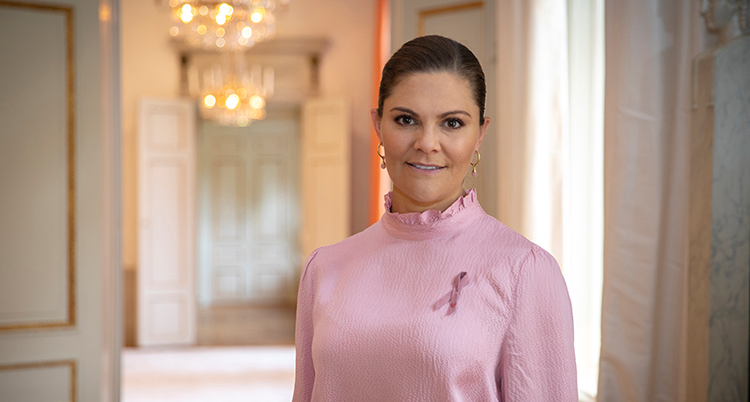 Hon har en rosa blus på sig. På bröstet sitter det Rosa bandet fast.