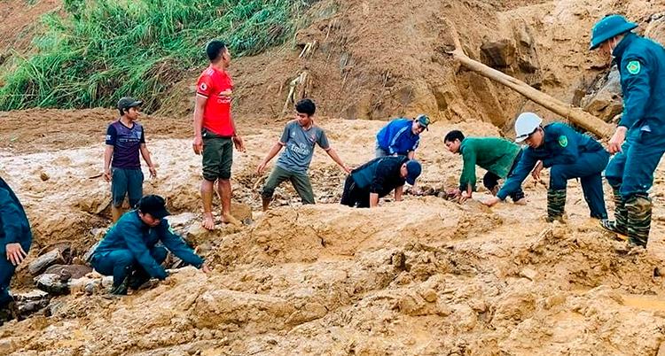 Ett tiotal människor håller på at gräva med händerna i lera. Det är nästan bara lera över hela marken. Det syns att den rasat ner från ett berg bakom dem.