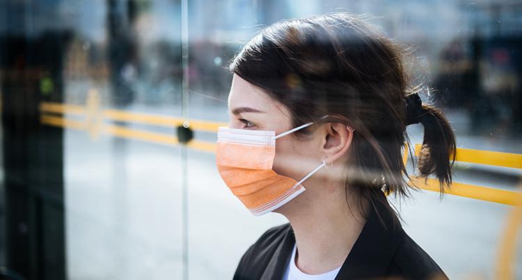 En kvinna har ett munskydd över munnen. Hon tittar åt sidan.