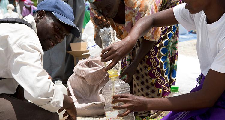 flera personer hjälps åt att hälla olja från en flaska till en annan. Det händer i Zimbabwe.
