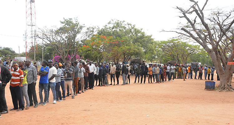 Människor står i en lång kö utomhus. De köar för att rösta i ett val. Marken ser ut som sand. Bakom kön finns några träd.