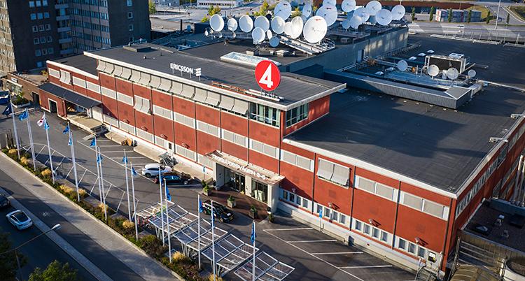 Vi ser TV4s hus i Stockholm. Det är ett stort rött hus. Ovanpå huset finns många parabolantenner. Bilden är tagen uppifrån.
