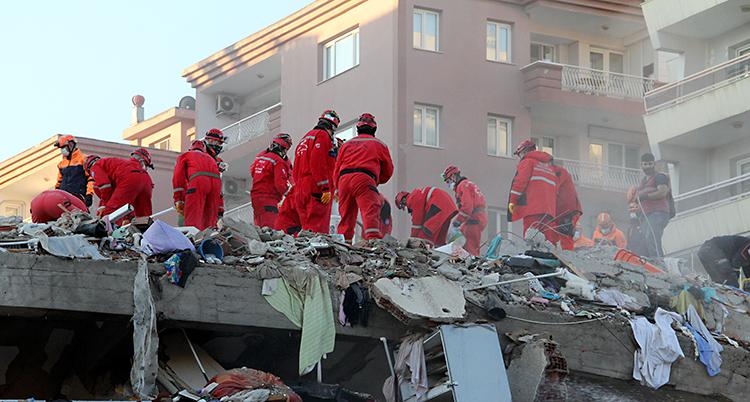Vi ser ungefär tio personer. De står ovanpå ett hus som har rasat. De har röda kläder och röda hjälmar.
