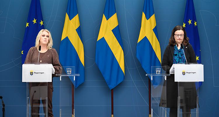 Två kvinnor står en scen. De pratar i varsin mikrofon. Lena Hallengren står till vänster och har ljust hår. Anna Ekström står till höger och har mörkt hår och glasögon. I bakgrunden finns Sveriges flagga och EUs flagga.