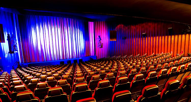 Bilden visar en salong på en biograf. Vi ser tomma rader med stolar. Längst fram är ett draperi.