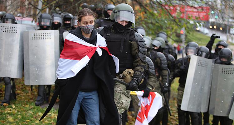 En polis går bakom en kvinna. Polisen har hjälm och mask för ansiktet. Kvinnan har en vit och röd flagga om axlarna.