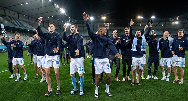 Flera män är på en fotbollsplan. De är glada och och dansar. De är spelare i Malmö FF.
