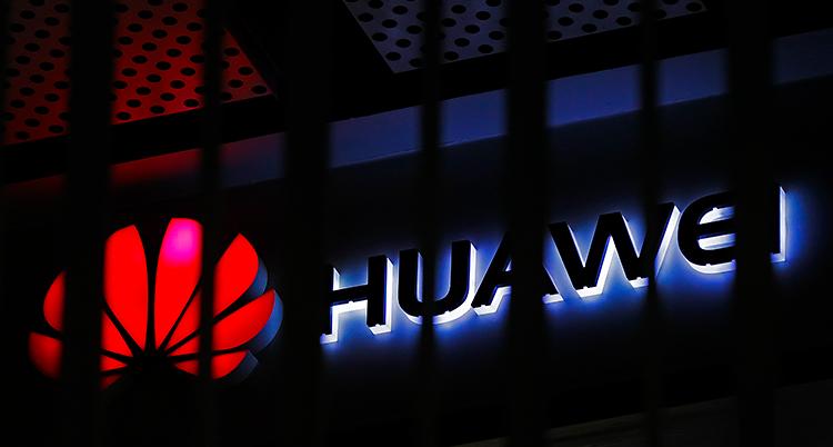 Bilden visar en skylt för företaget Huawei. Skylten lyser i mörkret. Det är en röd symbol och bredvid symbolen står det Huawei.